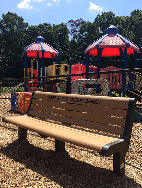 Color photograph of the Buddy Bench. Playground equipment is visible behind the bench.