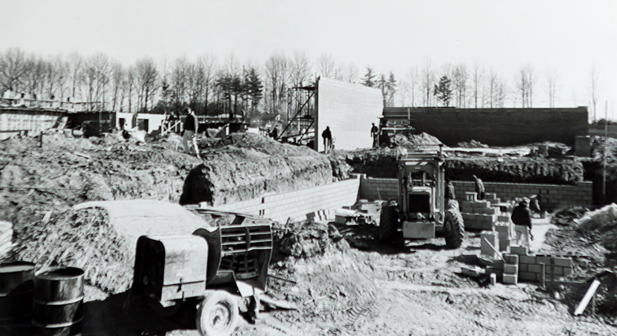 Black and white photograph of Camelot Elementary School taken in 1968 during construction of the building. Construction vehicles and supplies can be seen in the foreground. The cinderblock walls are starting to be erected. In the distance, tall trees without any leaves can be seen. Construction workers can be seen in different places around the site, working on the masonry.