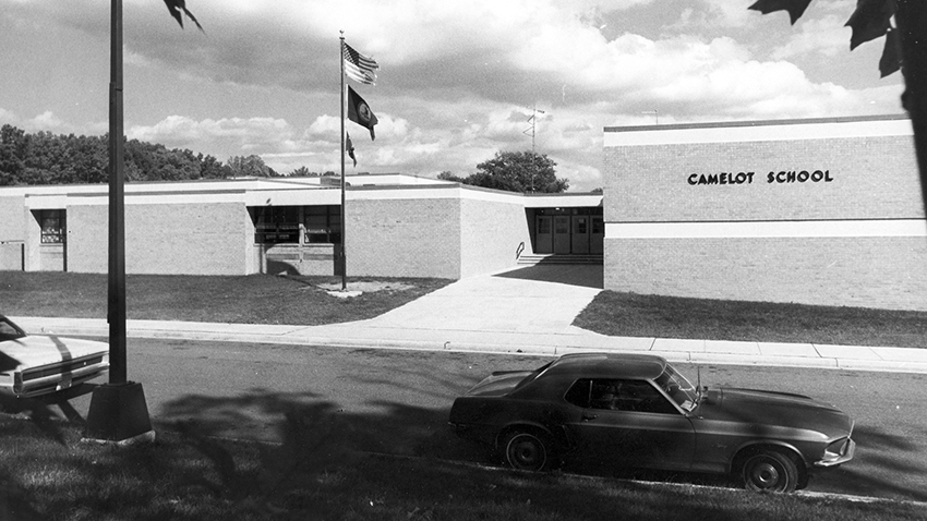Black and white photograph of the front exterior of Camelot Elementary School taken in the 1970s. The main entrance doors and flagpole are visible. Two cars are parked in front of the school. There are no bushes or shrubs in front of the building, so this picture may date from the earliest years after Camelot opened.