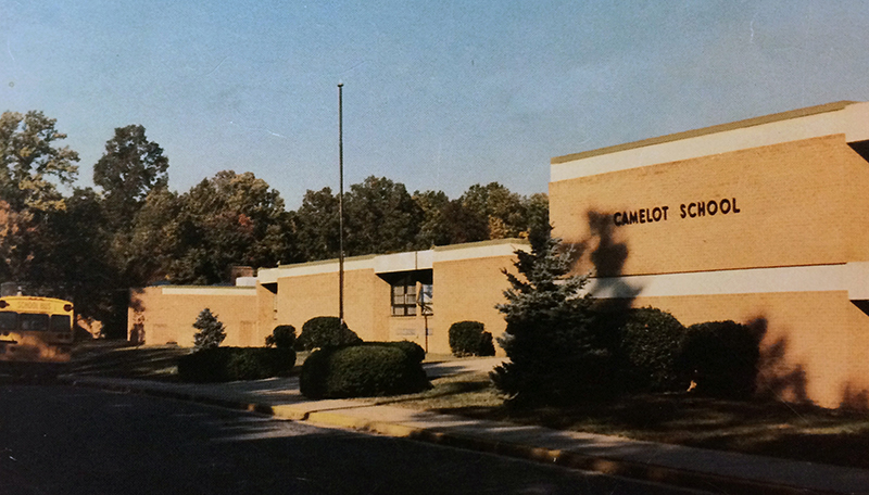 Color photograph of the front exterior of Camelot Elementary School from our 1981 to 1982 yearbook. Several large shrubs and a pair of evergreen trees have been planted in front of the school. A school bus can be seen on the far left, parked in front of the building.