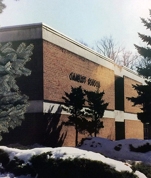 Color photograph of the front exterior of Camelot Elementary School from our 1999 to 2000 yearbook. Two large evergreen trees can be seen on the left and right side of the picture. In the center, the shrubs in front of the school are covered with snow. The sun is shining on the side of the building, casting long shadows.
