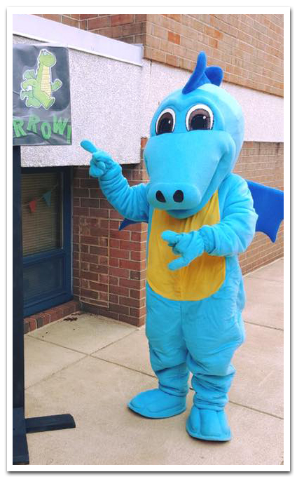 Photograph of an unknown person wearing the Flames mascot costume. The dragon costume has light blue fabric on the arms, legs, and head, dark blue fabric on the wings, and gold fabric on the belly. The mascot is standing on the sidewalk in front of our school pointing to an illustration of Flames on a sign.