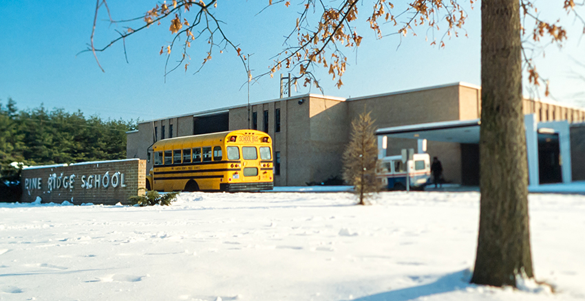 Color photograph of the front exterior of Pine Ridge Elementary School taken around 1980. A school bus and U.S. postal truck are parked in front of the building. There is snow on the ground and the trees in the foreground have lost most of their leaves.